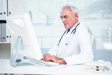Thoughtful doctor working on computer