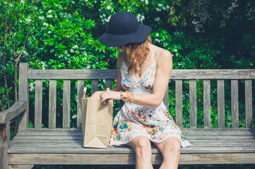 Young woman sitting on bench with paper bag