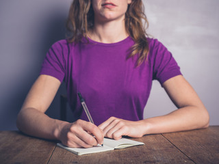Thoughtful young woman writing in notepad