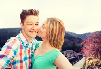 couple kissing and taking selfie over asian town