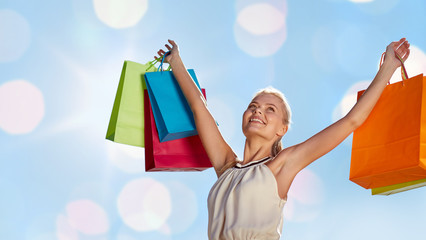 smiling woman with shopping bag rising hands