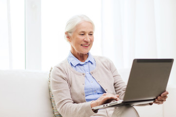 happy senior woman with laptop at home
