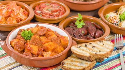Tapas - Selection of latin dishes. Chorizo al vino, Higados de pollo, Chicken and chorizo, Tomates al ajillo, Arroz con pollo, Camarones enchilhados, Patatas a ala riojana and Stuffed mushrooms.