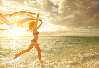 Happy carefree woman running in the sunset on the beach.