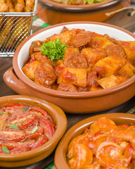 Patatas a la Riojana - Potato, chorizo and peppers stew. Surrounded by other tapas dishes.