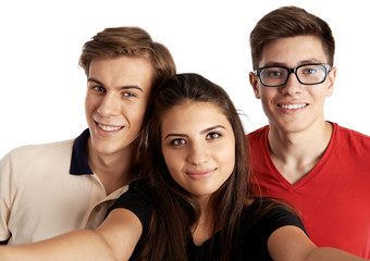 Attractive teenage friends making selfie looking at camera. Smiling people with smartphone photographing themselves.