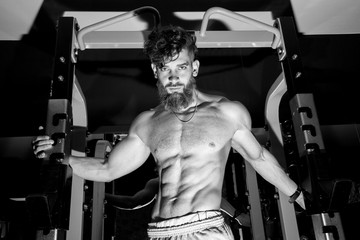 Muscular man with the beard training in the gym