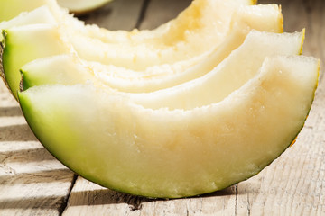 Ripe sliced  melon on a wooden background, selective focus