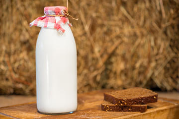 bottle of milk and a piece of rye bread on a straw background
