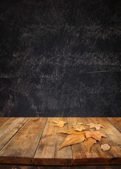 autumn background of fallen leaves over wooden table and blackboard background with room for text