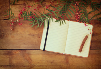open blank vintage notebook and wooden pencil over wooden table. ready for mockup. retro filtered image