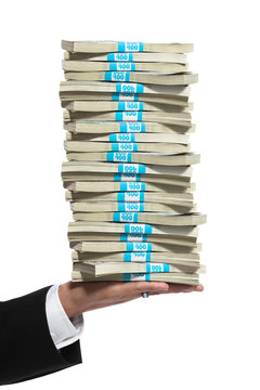 Hand of a business man holding a tall stack of money