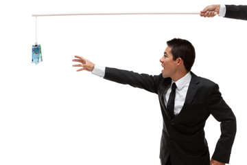 Businessman reaching for euros hanging from a stick