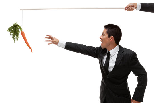 Businessman reaching for a carrot at the end of a stick