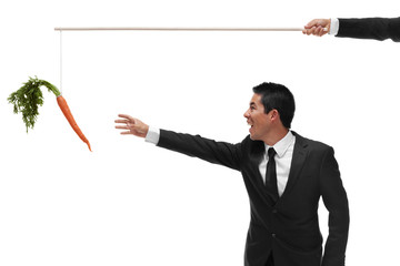 Excited businessman reaching for a carrot on the end of a stick