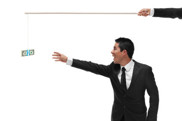 Excited businessman reaching for a stack of money on the end of
