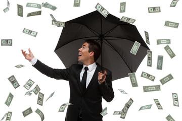Business man with umbrella raining money