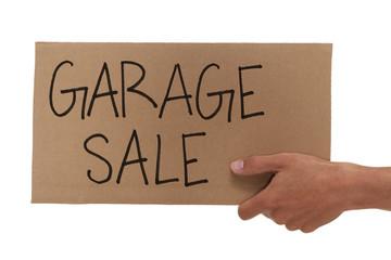 Hand holding up a cardboard garage sale sign