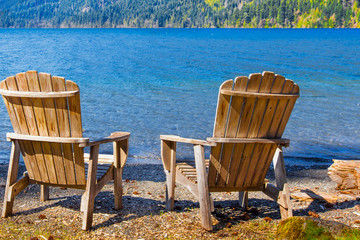 Two rustic wooden chairs by the side of a blue mountain lake
