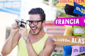 Colorful picture of a hipster young man in holidays taking pictures next to a destination sign
