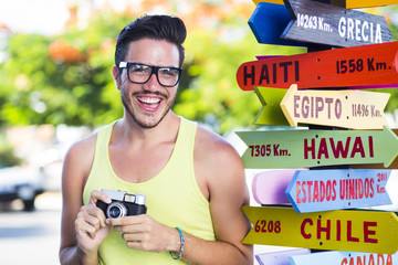 Colorful picture of a hipster young man in holidays taking pictures next to a destination post