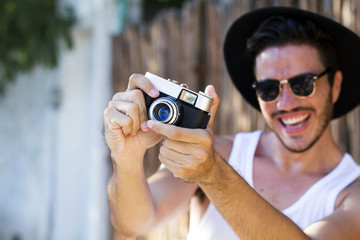 Hipster young man with vintage camera outdoors