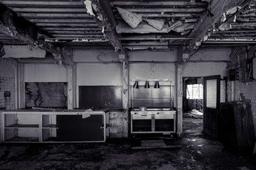 Black and white derelict abandoned kitchen, with severely ruined ceiling
