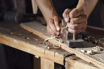 carpenter planing a plank of wood with a hand plane
