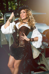 Beautiful elegant woman dressed in steampunk style posing over retro car
