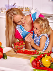Child feed mother  at kitchen.