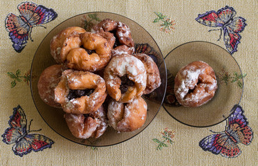 A lot of homemade donuts with cherry in a big black plate on tablecloth with butterflies . Aerial view.