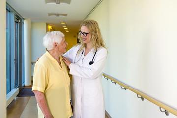 Nurse Assisting Elderly Woman Walking at Corridor.