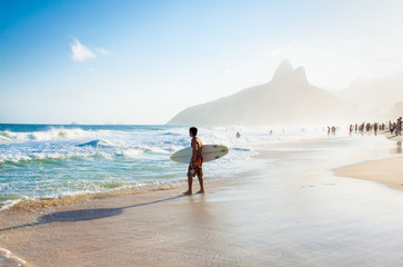 Brazilian surfer walking with surfboard toward Two Brothers Moun