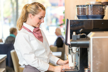 Waitress working at coffee machine in bakery or cafe