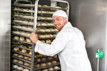 Baker at bakery putting rack of fresh dough in refrigerator