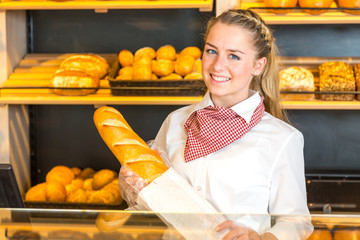 Shopkeeper at bakery putting loaf of bread into paper bag