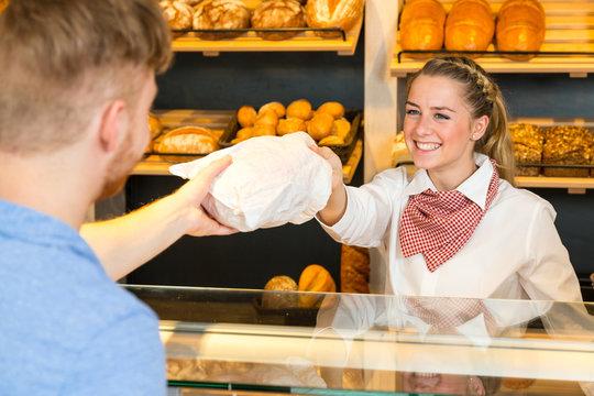 Shopkeeper in bakery hand bag of bread to customer