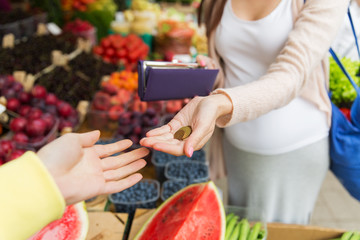 pregnant woman with wallet buying food at market