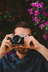 Male Photographer With Camera in front of Purple Flowers