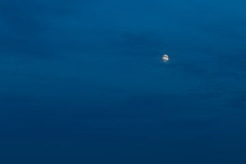 Beautiful almost fool moon on dark evening sky with clouds