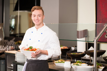 cook or chef from catering service posing with food at buffet