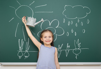 girl with watering can drawing on school board