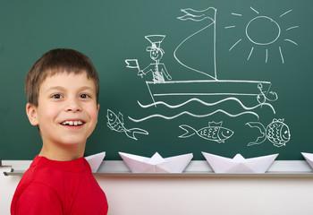 boy drawing ship on school board