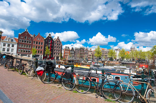 Amsterdam, the Netherlands-April 27: Traditional Amsterdam cityscape with medival houses, bikes on the bridge on April 27,2015. Amsterdam is the most populous city of the Kingdom of the Netherlands.