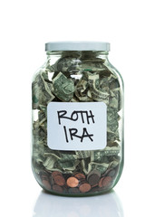 Glass jar full of money with a white ROTH IRA label