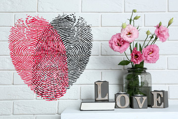 Beautiful flowers in vase with word Love and fingerprint heart