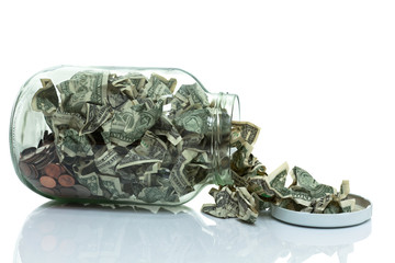 Glass jar full of money tipped over on its side spilling money w