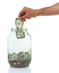 hand putting dollar bill into an empty jar