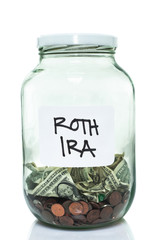 Glass jar with with a white ROTH IRA label and some money in it