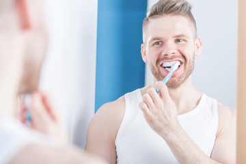 Narcissistic male brushing teeth